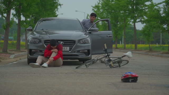 vidéos et rushes de man fallen from the bicycle sitting on the road after a car accident - accident bénin
