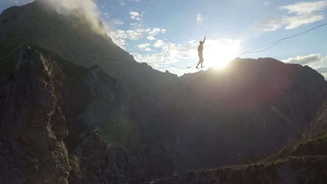 man falling down from a highline in the alps