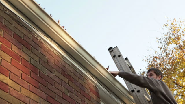 stockvideo's en b-roll-footage met man falling off ladder while cleaning gutters - slow motion - ladder gefabriceerd object