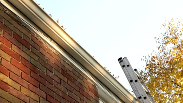 stockvideo's en b-roll-footage met man falling off ladder while cleaning gutters - ladder gefabriceerd object