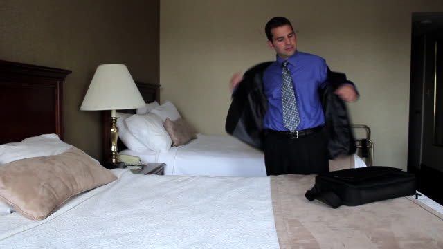 MS Man falling on bed at hotel room / Portland, ME, United States