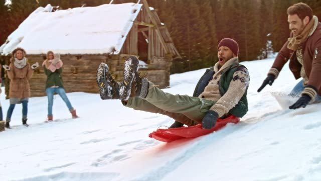 slo mo man falling to the ground while pushing his laughing male friend down the hill on a sledge - pushing stock videos & royalty-free footage