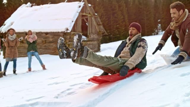そりで丘を下って彼の笑いの男性の友人を押しながら地面に落ちて slo mo 男 - ウィンターコート点の映像素材/bロール