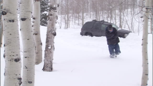 A man falls as he struggles to walk through deep snow during a blizzard.