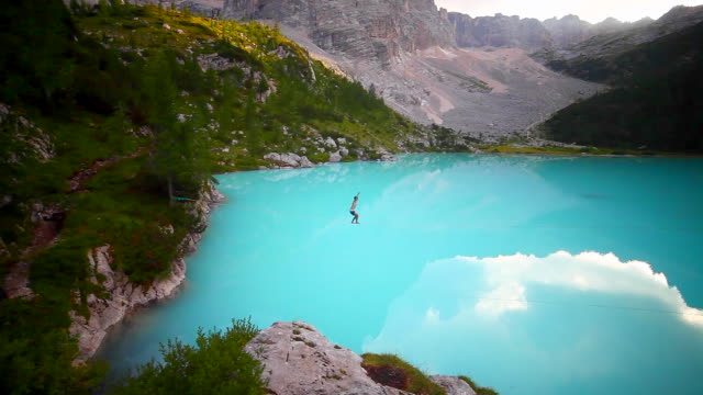 a man falls while slacklining on a tightrope and walking over a lake. - tightrope stock videos & royalty-free footage