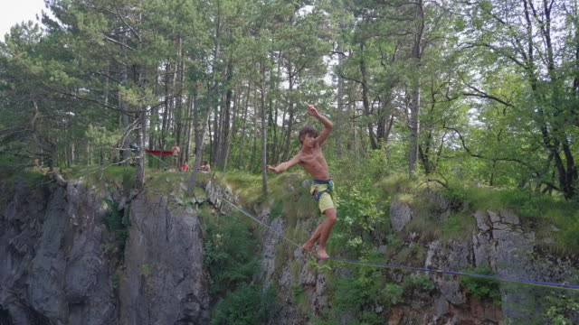 a man falls while slacklining on a tightrope in the mountains. - acrobatic activity stock videos and b-roll footage