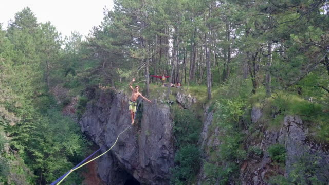 a man falls while slacklining on a tightrope in the mountains. - tightrope stock videos & royalty-free footage