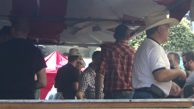 man fanning himself with a cowboy hat surrounded by men in cowhats under the tent of a market booth other cowboys taking to customers - cowboy hat stock videos & royalty-free footage