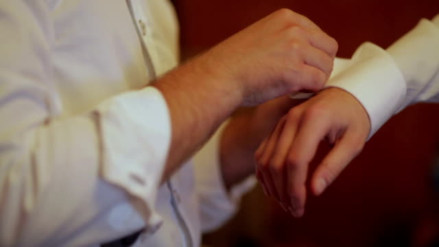 CLOSE UP Man fastening cufflinks on groom's cuff