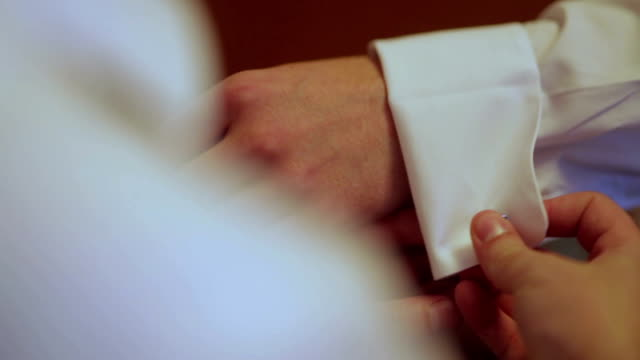 CLOSE UP SELECTIVE FOCUS Man fastening cufflinks on groom's cuff
