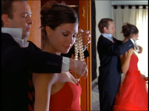 ms profile man fastening pearls around neck of woman in formal red dress / mirror reflection in background - red dress stock videos & royalty-free footage