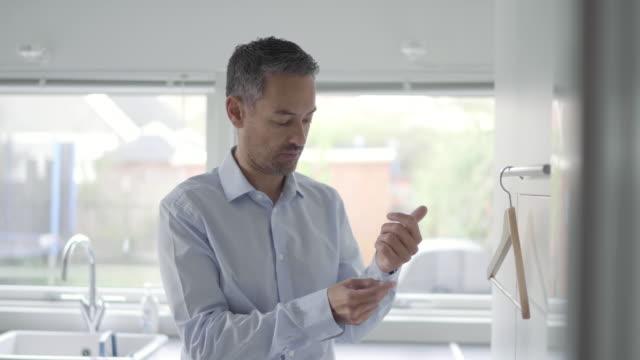 man fastening shirt - ハンガー点の映像素材/bロール