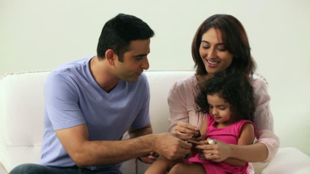 man feeding chocolate to his daughter  - maharashtra stock-videos und b-roll-filmmaterial