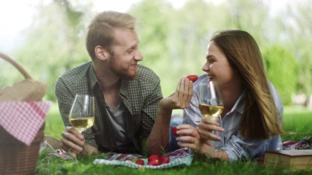 Man feeding girlfriend with strawberries on picnic at nature