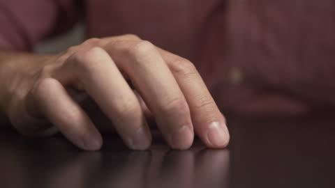 vídeos y material grabado en eventos de stock de el hombre se siente nervioso y tocando su dedo en la mesa.preocupación, deprime - dedo