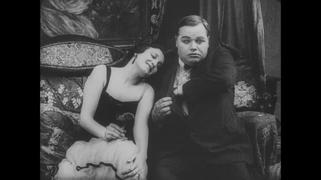 1917 man (fatty arbuckle) feels the effects of strong drink as woman rests drowsily on his shoulder - fatty arbuckle stock videos and b-roll footage