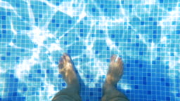 Man Feet in Sunlit Swimming Pool