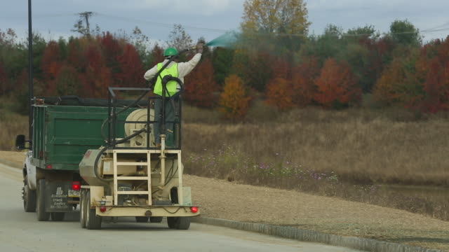 man fertilizes soil from moving truck, wide shot - insecticide stock videos & royalty-free footage