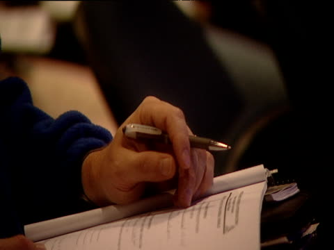 Man fiddles with pen whilst listening to lecture