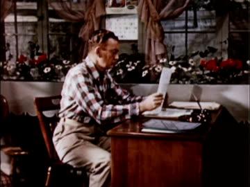 1956 ms ds man filing papers at desk, standing up, walking over to end table, browsing through magazine / usa - korrespondens bildbanksvideor och videomaterial från bakom kulisserna