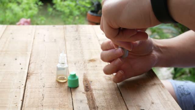 vídeos y material grabado en eventos de stock de hombre llenando un cigarrillo electrónico de e-juice - boquilla producto relacionado con el tabaco