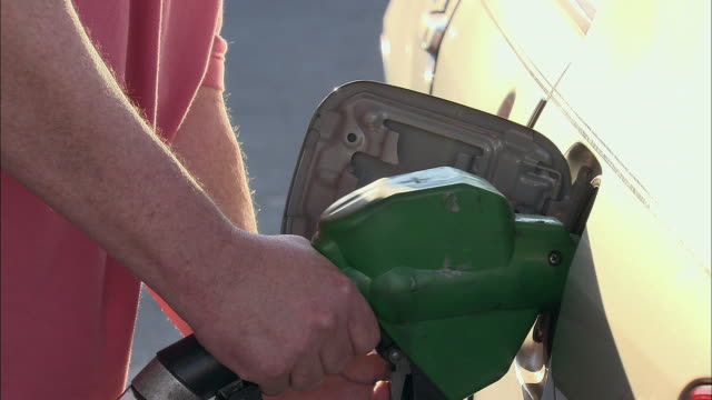 CU, Man filling car at Manhattan gas station, close-up of gas nozzle and hand, New York City, New York, USA