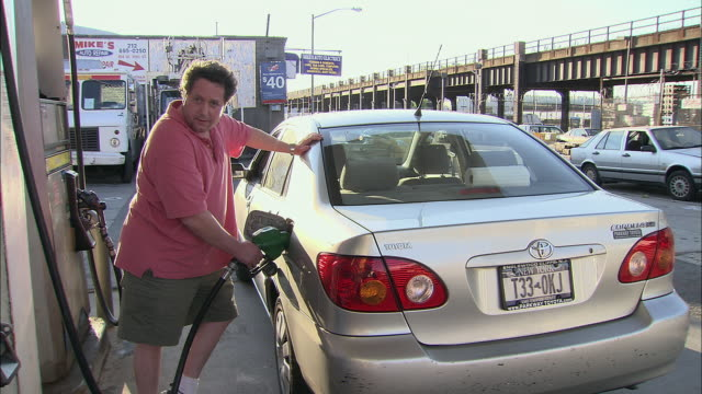 MS, Man filling car at Manhattan gas station, New York City, New York, USA