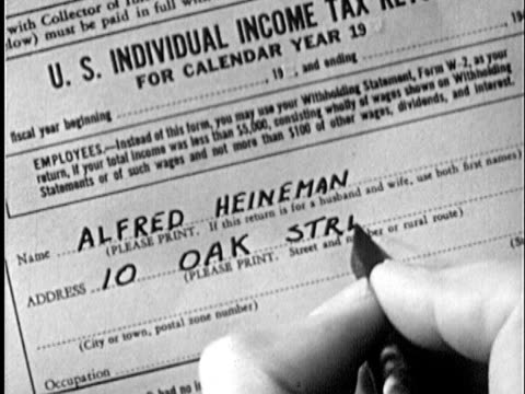 stockvideo's en b-roll-footage met 1951 b/w cu man filling out income tax form  - tax