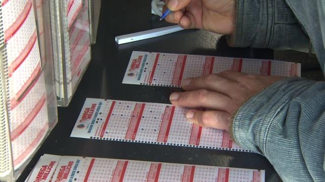 stockvideo's en b-roll-footage met man filling out mega millions lottery ticket on december 13, 2013 in los angeles, california - loterijlootje