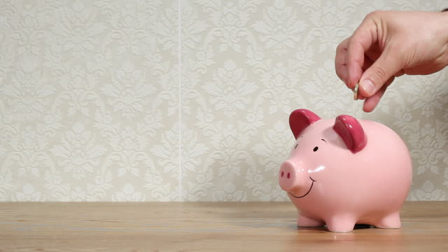 man filling piggy bank - piggy bank stock videos & royalty-free footage