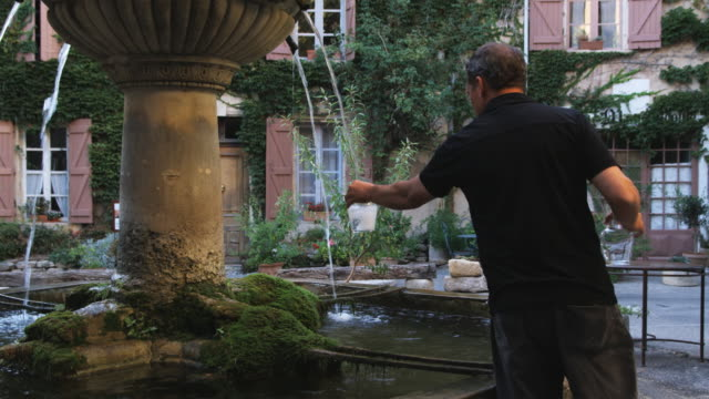 man filling up water jars from a fountain - saignon video stock e b–roll
