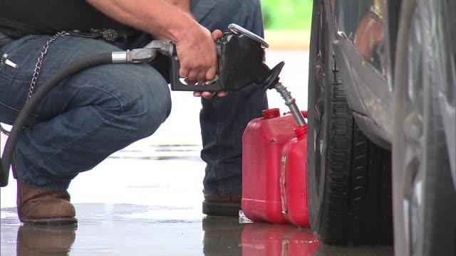 vídeos de stock e filmes b-roll de man fills up a gas can at a gas station in carolina beach, north carolina on september 16, 2018. - gas station