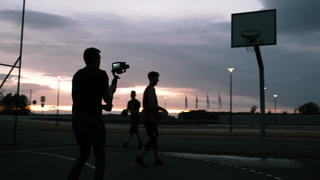 ms man filming basketball players shooting hoops on outdoor basketball court at dusk - cinematographer stock videos & royalty-free footage