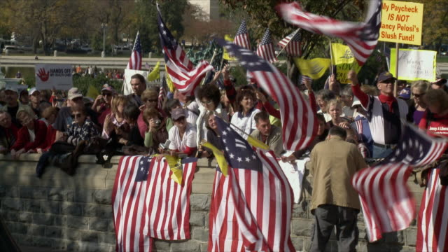vídeos y material grabado en eventos de stock de man filming group of protesters waving american flags at political rally against health care legislation on november 5th, 2009 / capitol hill,... - 2009