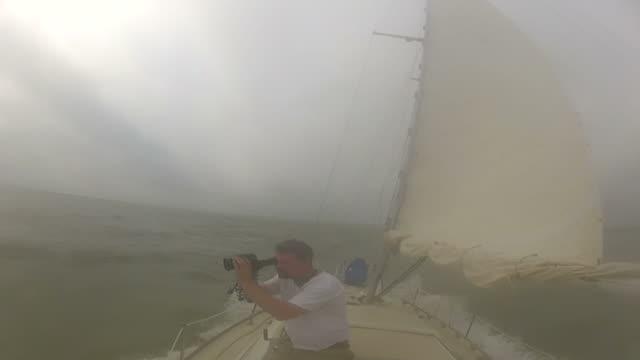 man filming while on sailboat in rough water - endast en medelålders man bildbanksvideor och videomaterial från bakom kulisserna