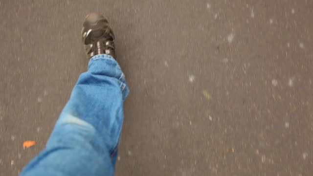 A man films his legs and feet walking down a street (POV)