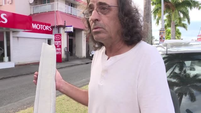 vídeos de stock, filmes e b-roll de a man finds a piece of metal on the shore of reunion island near to where a boeing 777 wing part believed to belong to missing flight mh370 washed up... - ilhas mascarene