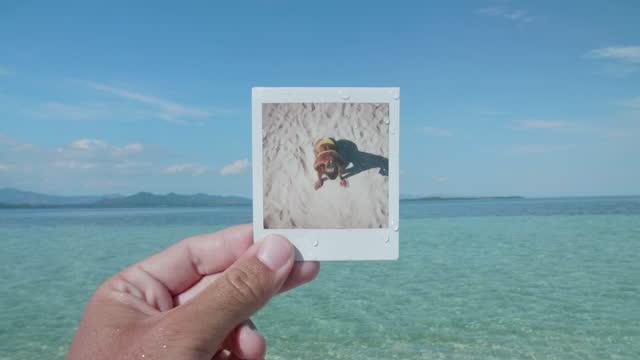 vídeos y material grabado en eventos de stock de a man finds a polaroid instant print photograph of a woman washing ashore at the beach while traveling. - slow motion - transferencia de impresión instantánea