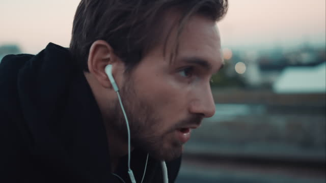 stockvideo's en b-roll-footage met man finishs jogging in urban setting - hoofdtelefoon