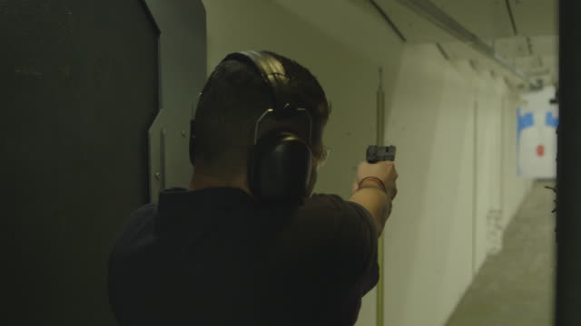 man fires handgun at shooting range, medium shot - target shooting stock videos & royalty-free footage