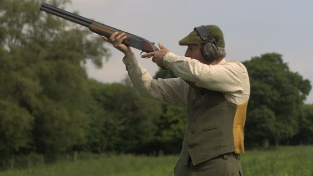 man fires shotgun and ejects cartridge - clay pigeon shooting stock videos and b-roll footage