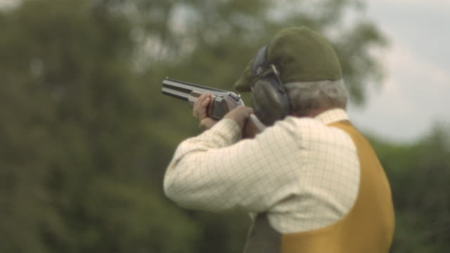 man fires shotgun rear view - tiro al piattello video stock e b–roll