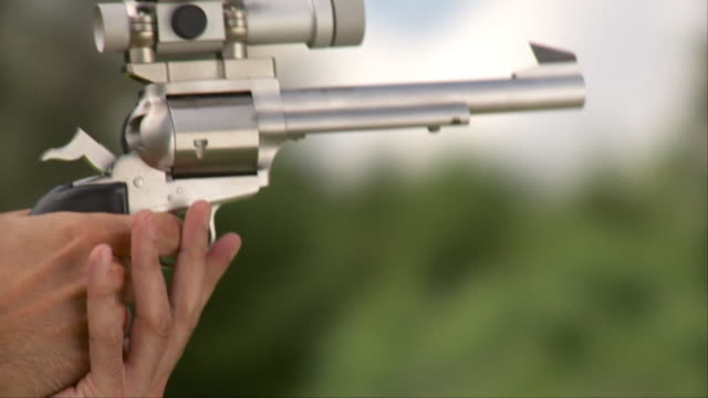 SLO MO ECU Man firing revolver with laser scope, Stowe, Vermont, USA