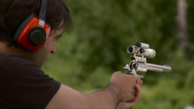 slo mo cu man firing revolver with laser scope, stowe, vermont, usa - fadenkreuz stock-videos und b-roll-filmmaterial