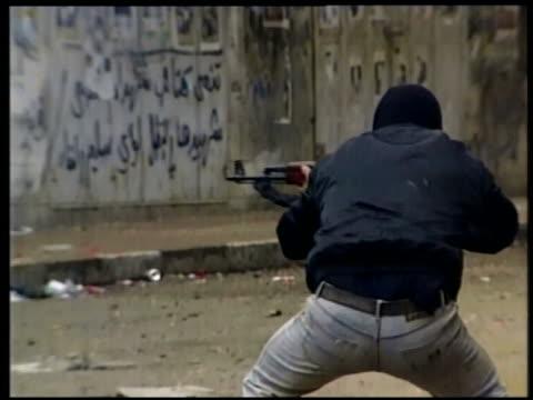 stockvideo's en b-roll-footage met ms man firing rifle on street / jerusalem - israëlisch palestijns conflict