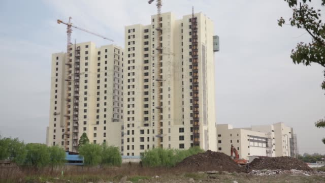 stockvideo's en b-roll-footage met a man fishes at a pond near residential buildings in the jiading district of shanghai china on monday april 11 residential buildings stand in the... - bulldozer