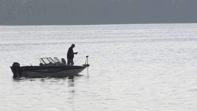 A man fishes from a drifting boat