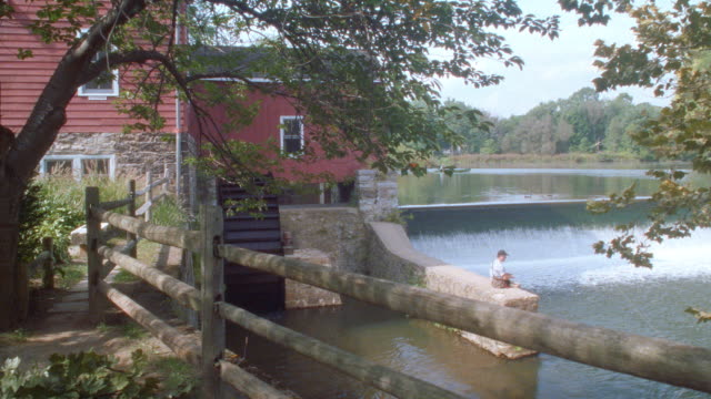 a man fishes in a pond near a mill. - mill stock videos & royalty-free footage