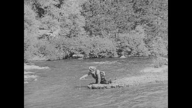 vídeos de stock, filmes e b-roll de 1923 man (buster keaton) fishes in river without a pole - 1923