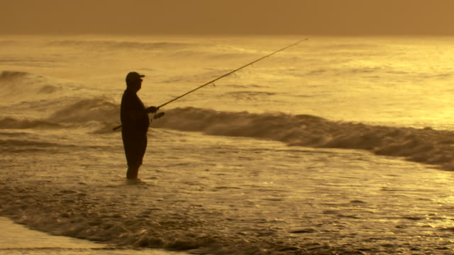 A man fishes in the ocean early morning.  The tide breaks around his legs. Golden Sky
